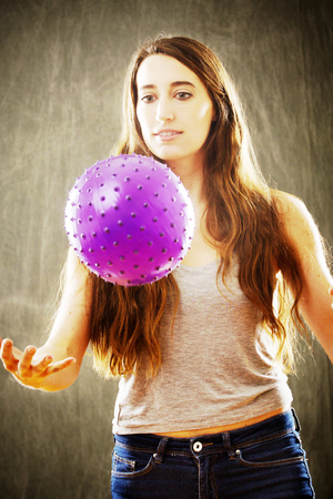 Sunny, high contrast image of attractive young woman with long brown hair playing with a purple ball in an orange glow.