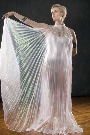 Beautiful young woman dancing in a shimmering transparent cape in the studio. Stock Photo
