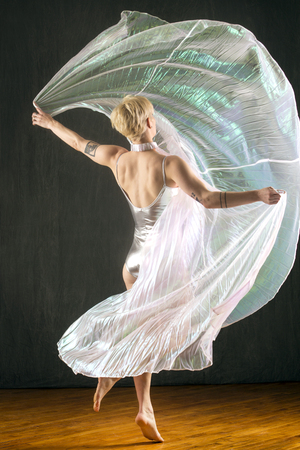 Beautiful young woman dancing in a shimmering transparent cape in the studio. Banque d'images