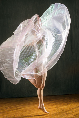Beautiful young woman dancing in a shimmering transparent cape in the studio. 스톡 콘텐츠
