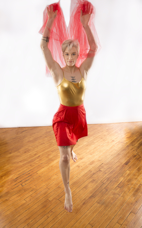 Nearly full length studio shot of beautiful young dancer in gold leotard and red skirt, with arms raised while twirling pink chiffon fabric in the studio.