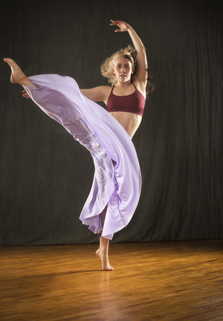 Full length studio shot of beautiful young dancer in burgundy top and lavender skirt, with arms raised while dancing in the studio.