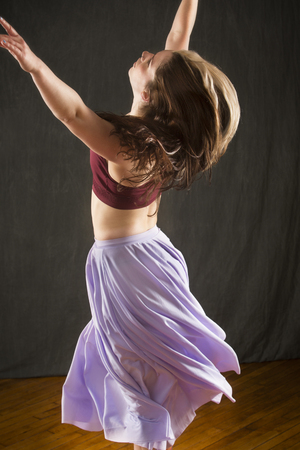 Nearly full length studio shot of beautiful young dancer in burgundy top and lavender skirt, with arms raised while dancing in the studio. Banco de Imagens