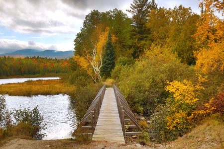 Autumn colors and a hiking bridge on the shoreline of Stratton Brook Pond in Carrabasset Valley, Maine.