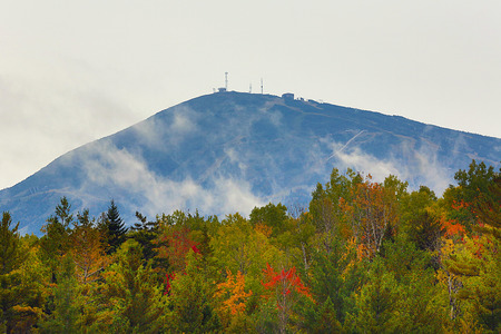 Sugarloaf Mountain in Kingfield, Maine, with autumn colors on the shoreline of Stratton Brook Pond.