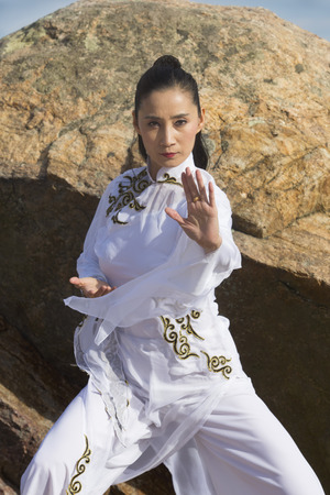 Young woman dancer in white gi performing qi gong on the rocky beach of Hammonasset State Park in Madison, Connecticut.