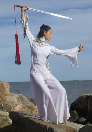 Young woman dancer in white gi performing qi gong with a sword on the rocky beach of Hammonasset State Park in Madison, Connecticut.