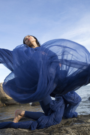 Graceful woman dancer in blue leotard and tights, hurling huge blue fabric into the wind on the beach at Hammonasset State Park in Madison, Connecticut. Imagens