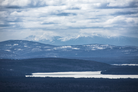 Cupsuptic Lake and frosty peaks of the White Mountains of New Hampshire seen from the summit of Bald Mountain in Oquossuc, Maine.