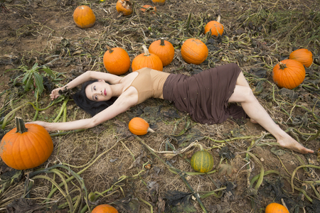 Adult woman dancer dressed in earth tones, lying stretched out among pumpkins in a farm field, in Ellington, Connecticut.