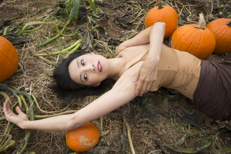 Half length adult woman dancer dressed in earth tones, lying stretched out among  pumpkins in a farm field, in Ellington, Connecticut. Stock Photo