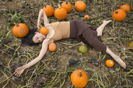 Adult woman dancer dressed in earth tones, lying stretched out in a farm field holding a pumpkin against her neck, in Ellington, Connecticut.