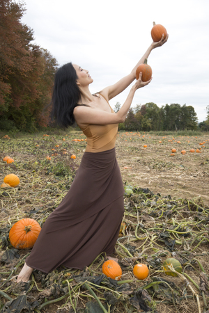 Adult woman dancer dressed in earth tones, standing in a farm field, reaching up with pumpkins in her hands, in Ellington, Connecticut.