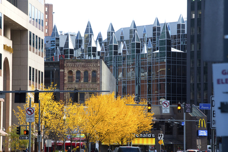 Pittsburgh, Pennsylvania / USA - November 7, 2018: Glass turrets mark a building in PPG Plaza in downtown, with fall foliage along the street.