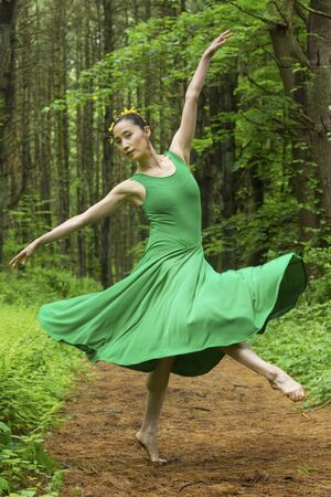 Woman in green dress,  dancing on a path in the woods, at the Belding Wildlife Management Area in Vernon, Connecticut. Stock fotó