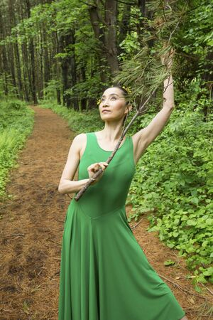 Woman dancing on a path in the woods, in green dress, holding a branch at the Belding Wildlife Management Area in Vernon, Connecticut. Stock fotó