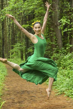 Woman dancer in green dress, leaping on a path in the woods, at the Belding Wildlife Management Area in Vernon, Connecticut.
