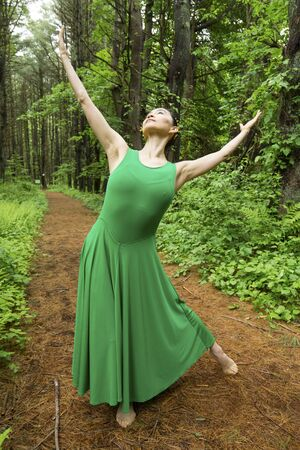 Woman in green dress,  dancing on a path in the woods at the Belding Wildlife Management Area in Vernon, Connecticut.