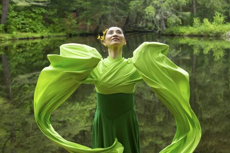 Woman in green dress with long flowing sleeves,dancing on a path in the woods near a pond, at the Belding Wildlife Management Area in Vernon, Connecticut. Foto de archivo - 130852839