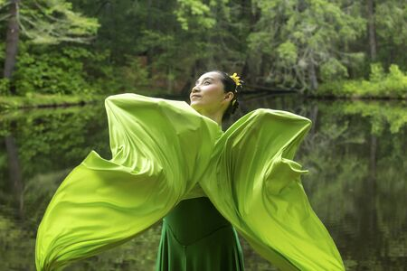 Woman in green dress with long flowing sleeves,dancing on a path in the woods near a pond, at the Belding Wildlife Management Area in Vernon, Connecticut. Stock fotó