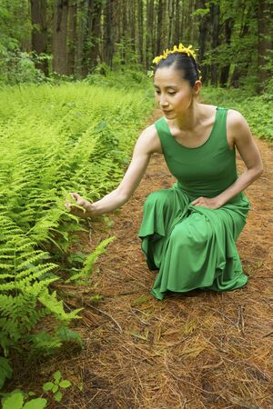 Woman dancer in green dress, looking at fern leaves along a path in the woods, at the Belding Wildlife Management Area in Vernon, Connecticut. Foto de archivo - 130852864