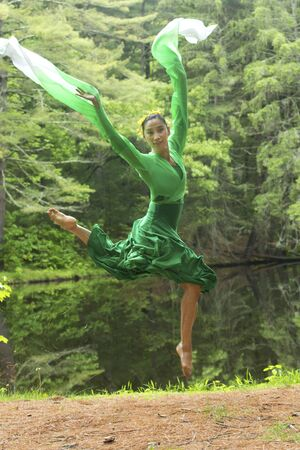 Woman dancer in green dress with long flowing sleeves, leaping on a path in the woods near a pond, at the Belding Wildlife Management Area in Vernon, Connecticut.