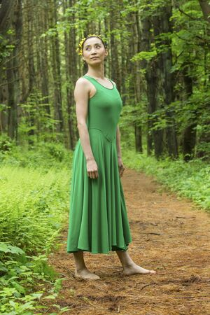 Woman dancer in green dress, standing on a path in the woods, at the Belding Wildlife Management Area in Vernon, Connecticut. Stock fotó