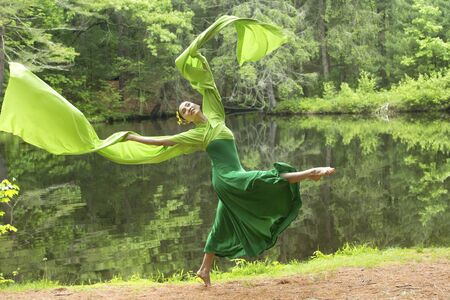 Woman in green dress with long flowing sleeves,dancing on a path in the woods near a pond, at the Belding Wildlife Management Area in Vernon, Connecticut. Foto de archivo - 130852875