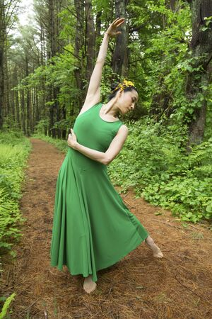 Woman in green dress,  dancing on a path in the woods at the Belding Wildlife Management Area in Vernon, Connecticut. Foto de archivo - 130852877