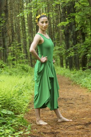 Woman dancer in green dress, standing on a path in the woods, at the Belding Wildlife Management Area in Vernon, Connecticut. Foto de archivo - 130852876