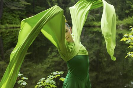 Woman in green dress with long flowing sleeves, dancing on a path in the woods near a pond, at the Belding Wildlife Management Area in Vernon, Connecticut. Foto de archivo - 130852879