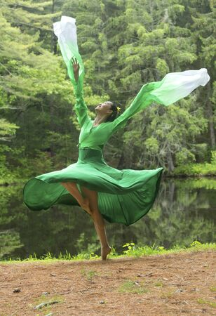 Woman dancer in green dress with long flowing sleeves, leaping on a path in the woods near a pond, at the Belding Wildlife Management Area in Vernon, Connecticut. Foto de archivo - 130852884