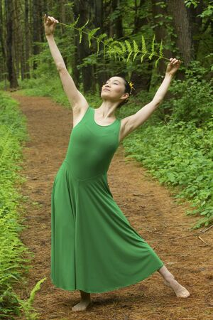 Woman in green dress,  dancing on a path in the woods while holding a fern leaf, at the Belding Wildlife Management Area in Vernon, Connecticut. Foto de archivo - 130852882