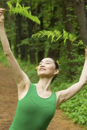 Woman in green dress,  dancing on a path in the woods while holding a fern leaf, at the Belding Wildlife Management Area in Vernon, Connecticut. Foto de archivo - 130852891