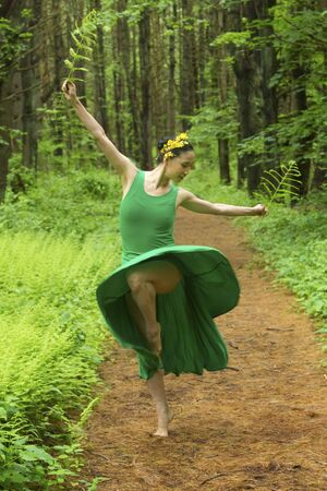 Woman in green dress,  dancing on a path in the woods while holding a fern leaf, at the Belding Wildlife Management Area in Vernon, Connecticut. Foto de archivo - 130852890