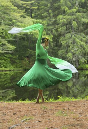 Woman in green dress with long flowing sleeves,dancing on a path in the woods near a pond, at the Belding Wildlife Management Area in Vernon, Connecticut. Foto de archivo - 130852894