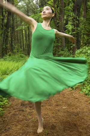 Woman in green dress,  dancing on a path in the woods at the Belding Wildlife Management Area in Vernon, Connecticut. Foto de archivo - 130852898