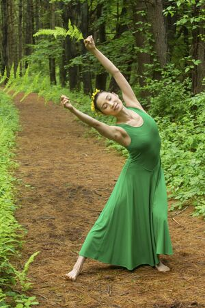 Woman in green dress,  dancing on a path in the woods while holding a fern leaf, at the Belding Wildlife Management Area in Vernon, Connecticut. Foto de archivo - 130852900