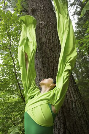 Woman in green dress with long flowing sleeves, dancing in the woods, at the Belding Wildlife Management Area in Vernon, Connecticut. Foto de archivo - 130852909