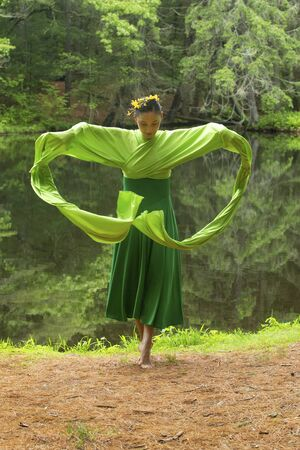 Woman in green dress with long flowing sleeves,dancing on a path in the woods near a pond, at the Belding Wildlife Management Area in Vernon, Connecticut. Foto de archivo - 130852916