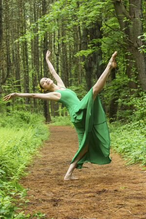 Woman in green dress,  dancing on a path in the woods, doing a high kick at the Belding Wildlife Management Area in Vernon, Connecticut. Foto de archivo - 130852917