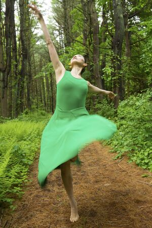 Woman in green dress,  dancing on a path in the woods at the Belding Wildlife Management Area in Vernon, Connecticut. Foto de archivo - 130852918