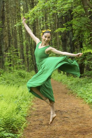 Woman dancer in green dress, leaping on a path in the woods, at the Belding Wildlife Management Area in Vernon, Connecticut. Foto de archivo - 130852920