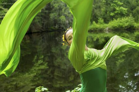 Woman in green dress with long flowing sleeves, dancing on a path in the woods near a pond, at the Belding Wildlife Management Area in Vernon, Connecticut. Foto de archivo - 130852925