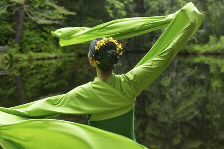 Woman in green dress with long flowing sleeves, dancing on a path in the woods near a pond, at the Belding Wildlife Management Area in Vernon, Connecticut.