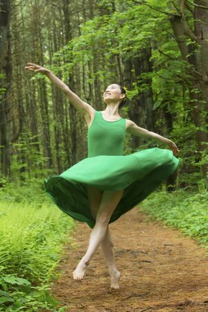 Woman in green dress,  dancing on a path in the woods, at the Belding Wildlife Management Area in Vernon, Connecticut. Foto de archivo - 130852924