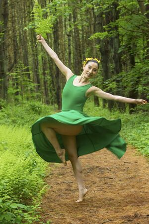 Woman in green dress,  dancing on a path in the woods while holding a fern leaf, at the Belding Wildlife Management Area in Vernon, Connecticut. Foto de archivo - 130852932