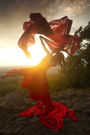 Female dancer in red dress, waving into the wind at sunset on the mountain a red fabric with Chinese calligraphy on it, at Penwood State Park in Bloomfield, Connecticut. Foto de archivo - 133024112