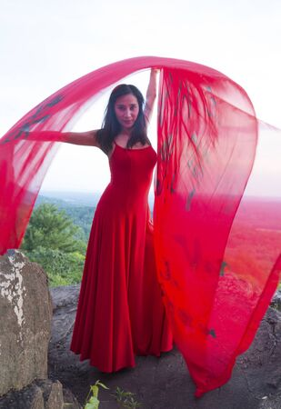 Female dancer in red dress, waving into the wind in late afternoon on the mountain, a red fabric with Chinese calligraphy on it, at Penwood State Park in Bloomfield, Connecticut. Foto de archivo - 133024118