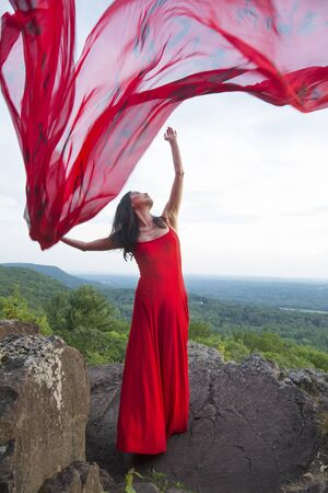 Female dancer in red dress, waving into the wind in late afternoon on the mountain, a red fabric with Chinese calligraphy on it, at Penwood State Park in Bloomfield, Connecticut. Foto de archivo - 131648897